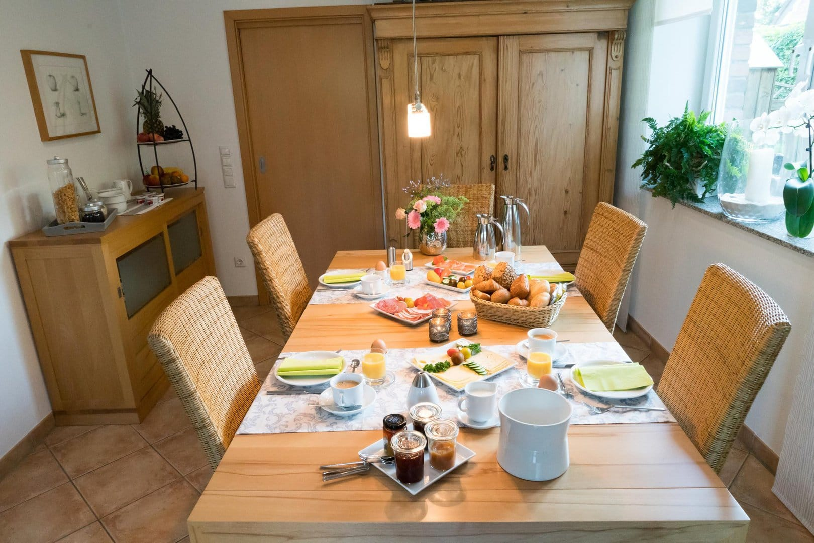 A wooden table set for four people with a selection of breads, meat and cheese, as well as various jams, yoghurts and coffee. The table stands in a bright room. In the background you can see chest of drawers which is set with mueslis and fruits.