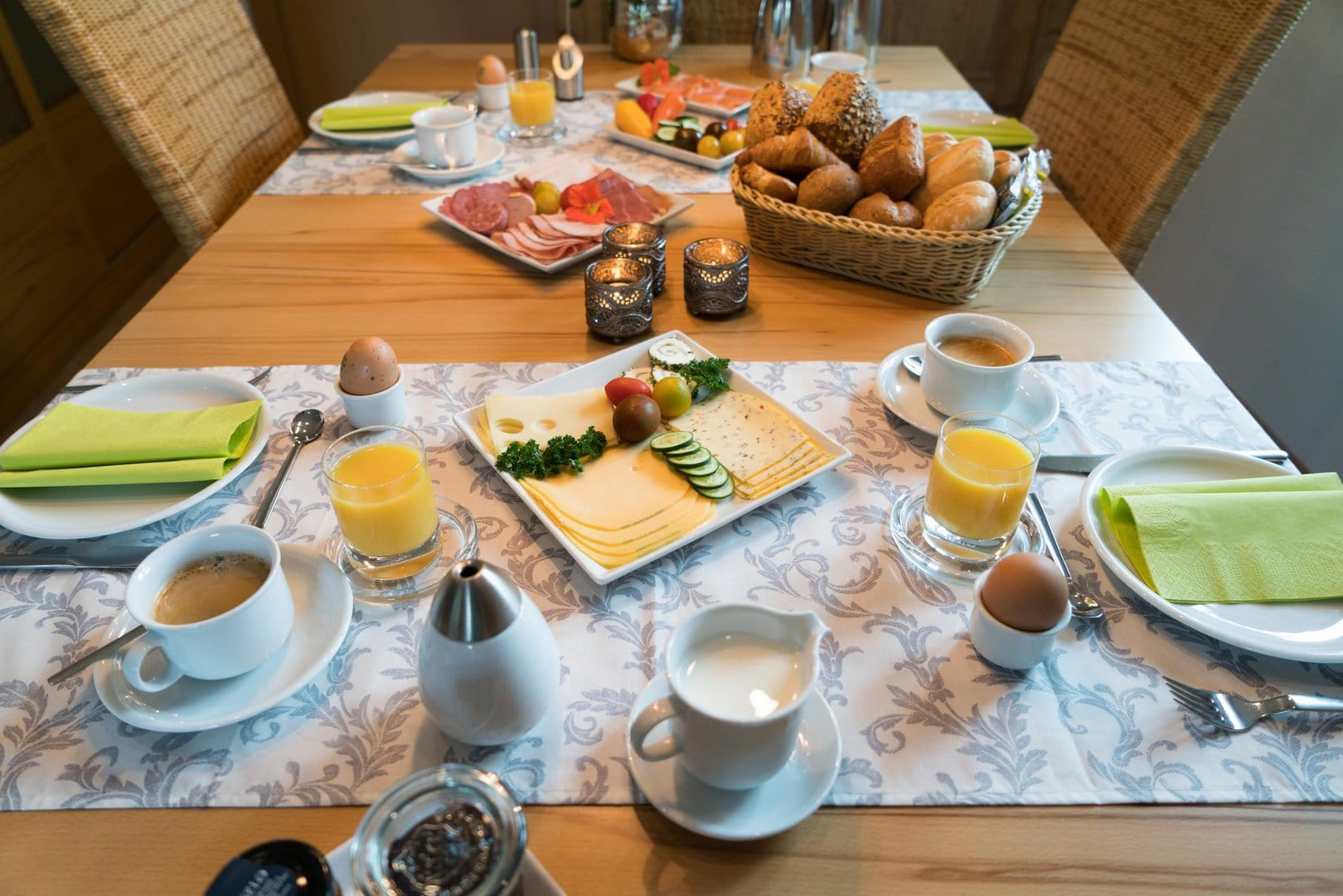 A breakfast table, generously set with coffee cups, eggs, orange juice, meats, cheeses and bread.