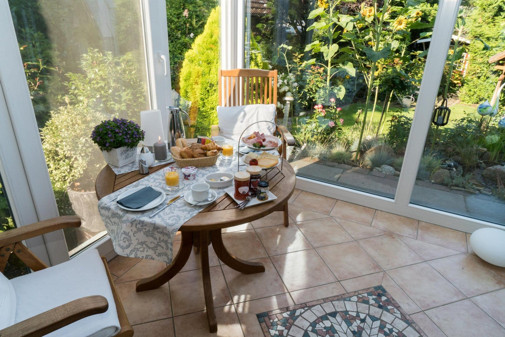 A wooden table set with a selection of breads, meat and cheese, as well as various jams, yoghurts and coffee. The table stands in a wintergarden, which is surrounded by a green garden.
