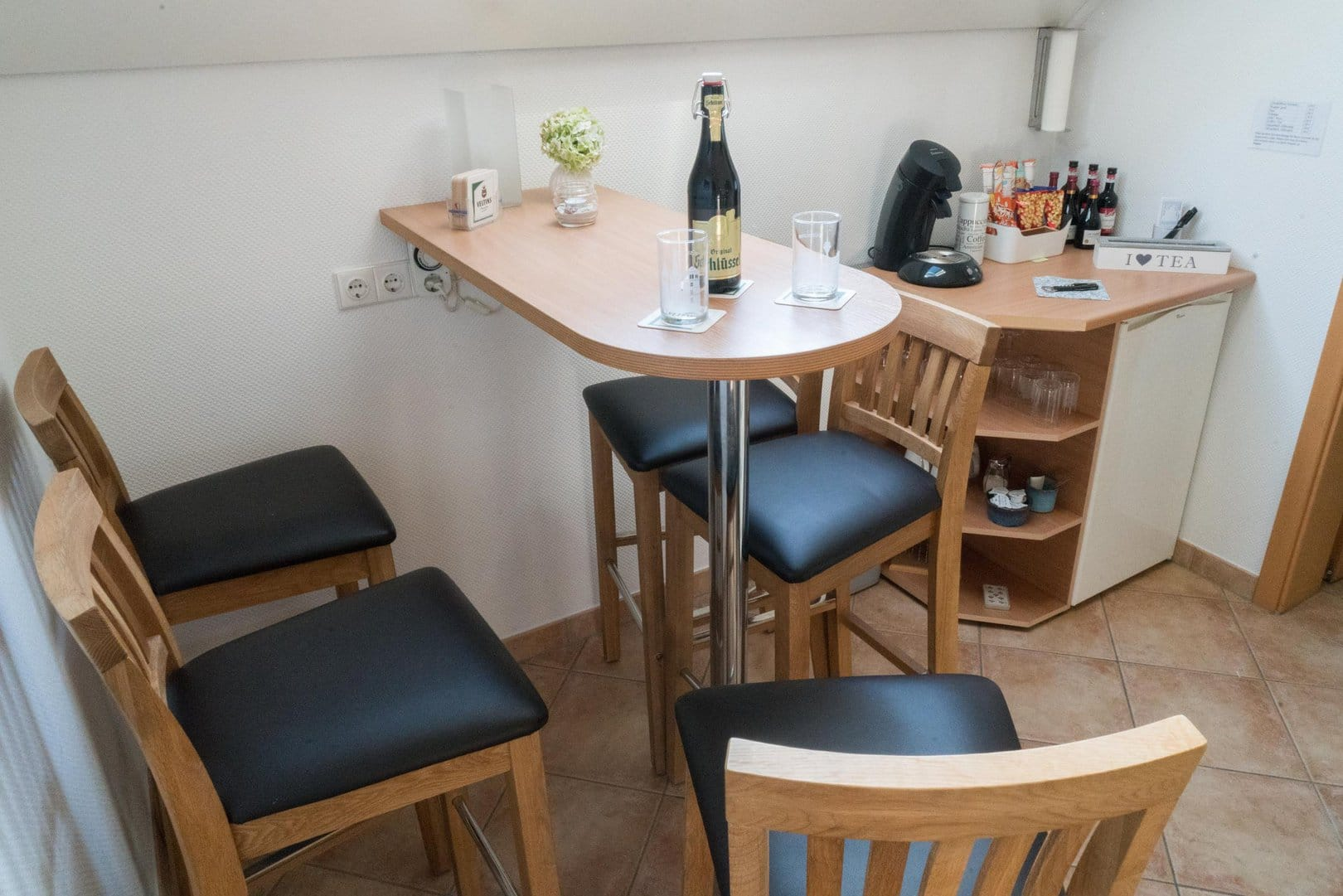 "Common room with a standing table and chairs. On it, a bottle of ""Altbier�. In the background you can see the minibar with a coffee machine, snacks, bottles of wine, as well as glasses and cups."