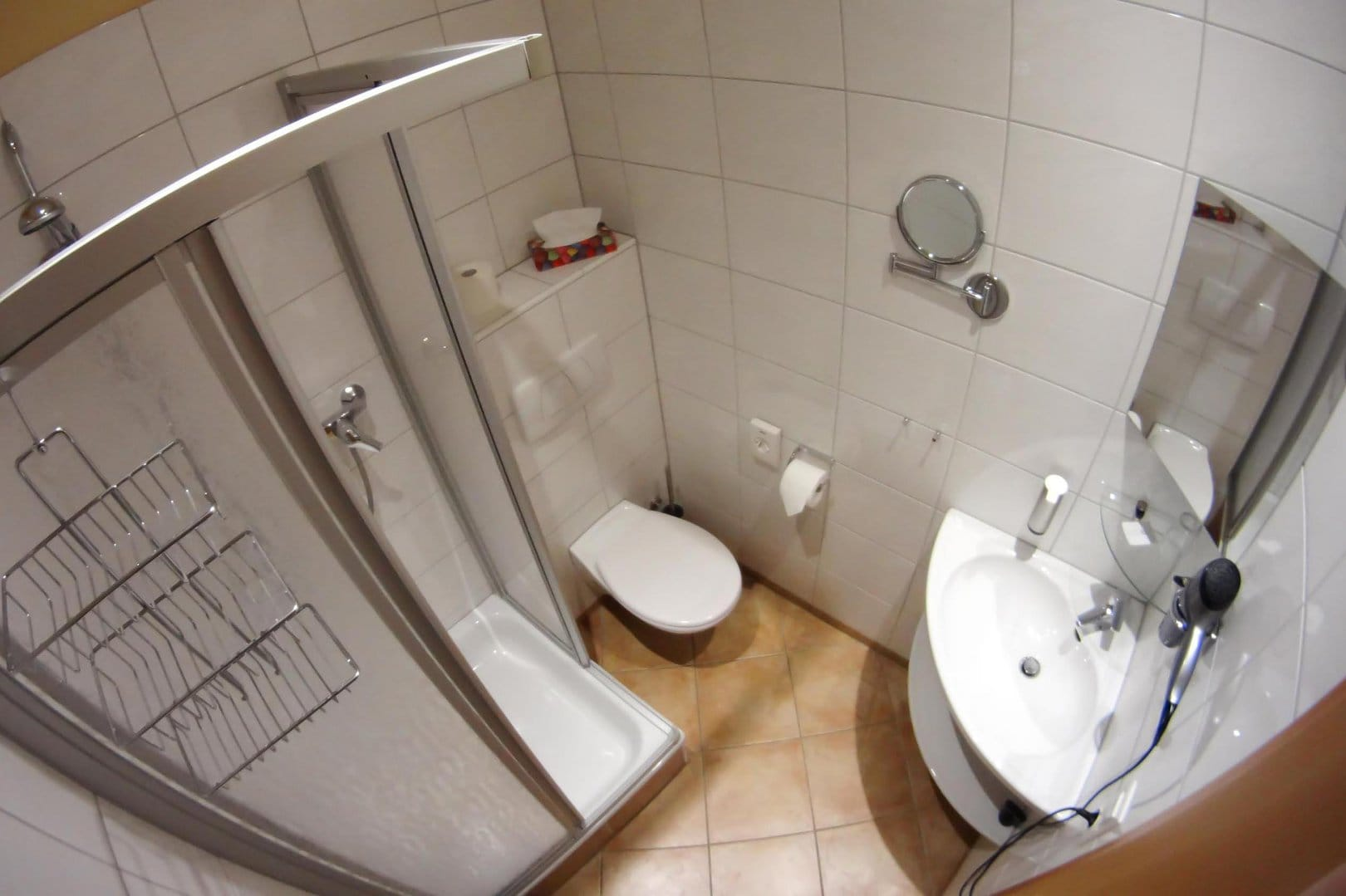 Small, bathroom with white tiles featuring a sink, a shower, a toilet, various mirrors and a hair dryer.