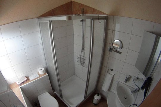 Small, bathroom with white tiles, a sink, a shower, a toilet, various mirrors and a hair dryer.