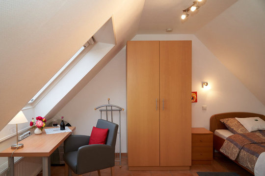 The attic room, featuring a single bed, a desk, a chair and a wardrobe.