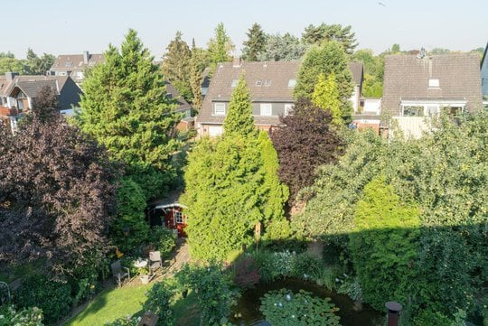 The view from the roof-top window shows the garden with its many trees the pond and the red shed.
