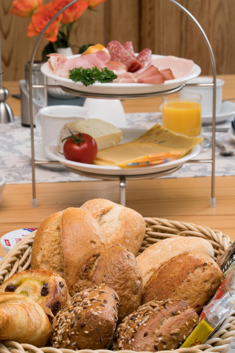 A basked of breads and an etagere with a meat- and cheese-selection, set on a breakfast table.